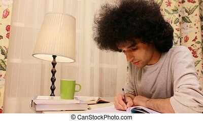 young man studying and writing on the book 2