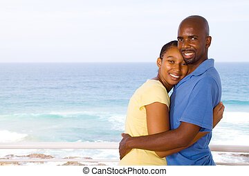 young happy african american couple hugging, background is...