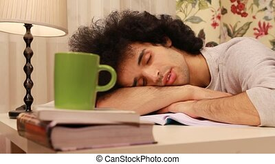 young man falling on a sleep while studying