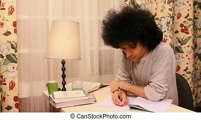 young man studying and writing on the book