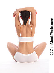 Behind toned young woman sitting arms raised - Fit and...