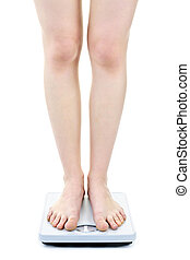 Woman standing on bathroom scale - Slender female legs...