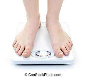 Feet on bathroom scale - Bare female feet standing on...