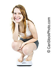 Smiling young girl on bathroom scale