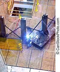 A welder creating an arc. - A welder creating an arc and...