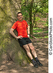 Smiling Man Resting against Tree - Smiling Middle AgeMan...
