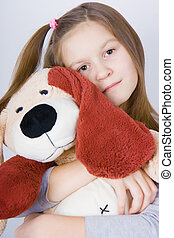Girl with toy dog - sad girl hugging a toy dog. Portrait of...