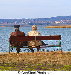 Elderly couple on a bench - Senior man and woman relaxing at...