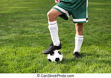 Cleets and ball on boy - Close up of a boys legs wearing...