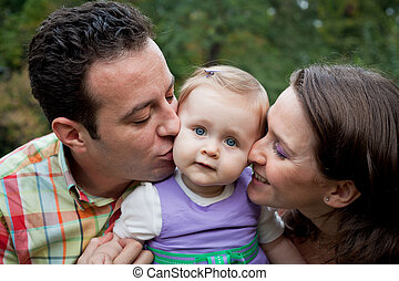 Family love - parents kiss for daughter