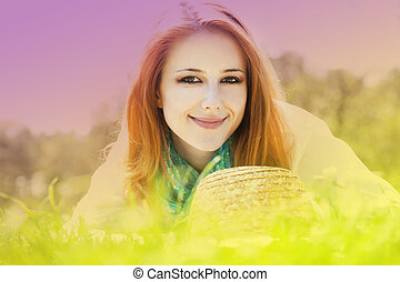 Redhead girl at grass in the park. Photo in multicolor style.