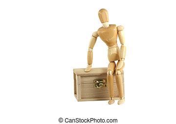 Wooden manikin on treasure chest