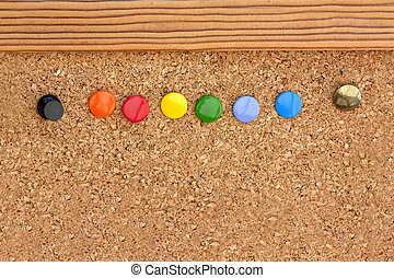 drawing pins in a cork pinboard - macro shot of coloured...