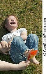 Laughing child being tickled under the feet with a colorful feather