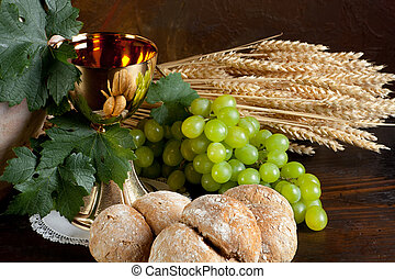 Bread and wine for communion - Grapes and holy bread next to...
