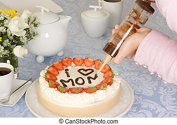 Mommy on a cake - Hands writing Mommy on a mothers day cake