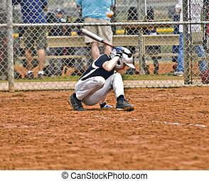 Boy Baseball Batter - A young boy at bat ducking away from...