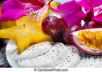 tropical fruits. Sliced dragon fruit, carambola, and grapes