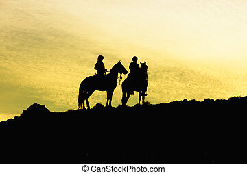 Silhouette of two horses with riders on a hill, against a...