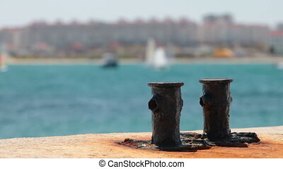 Rusty Bollard at Harbor in the background yachts and...