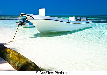 White motor boat on a sand beach in the ocean