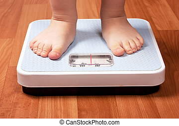 Scales - Closeup view of scales on a floor and kids feet