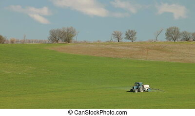 Tractor spraying field in spring