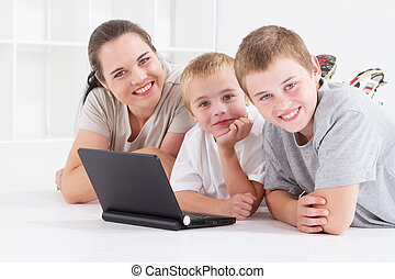 mother and kids using laptop - mother and her boys using...