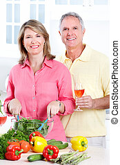 Seniors at kitchen - Happy seniors couple cooking at new...
