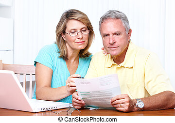 Senior couple reading the bills at new home.