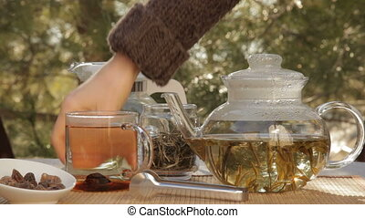 Woman mixes glass of tea outdoors, 5DII, 1080p, 2997 fps,...