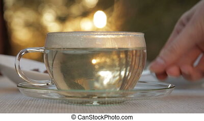 Woman mixes glass of tea outdoors