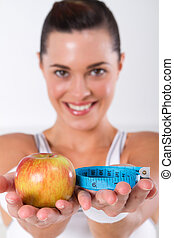 happy fitness woman with apple and measuring tape