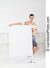 woman holding white board - young fitness woman holding...