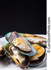 raw mussel on black background