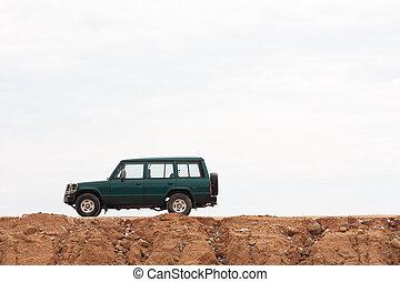 4WD car - Muddy 4WD car against white sky