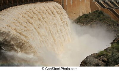 Dam wall with open sluice gates - Strong flowing water with...