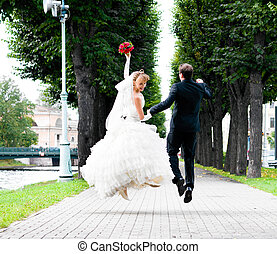 wedding jump - bride and groom is running with joined hands...