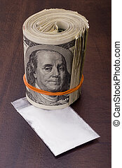 Drug Money - Roll of American money next to a sealed bag...