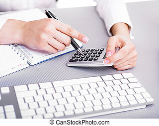 Calculating - Office business woman calculating with...
