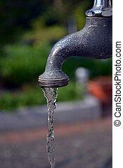 Running garden faucet tap close up