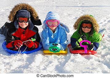 Children with slides - Three caucasian kids in winter...