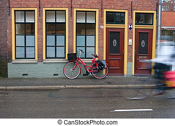 red bicycle parked against a house