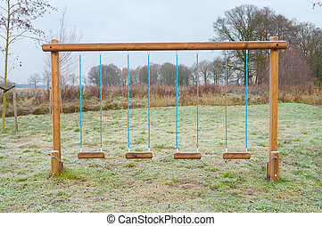 empty swing - four empty swings in winter time fixed with a...