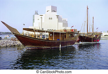 Two dhows and Qatar museum - The harbour in Doha, Qatar,...