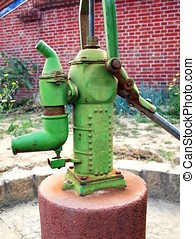 Old-Fashioned Pitcher Pump - A cast iron hand press pump in...