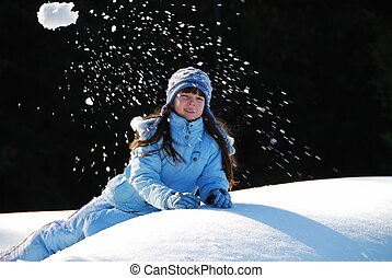 Girl Throwing Snow - A young child throwing a snowball in...