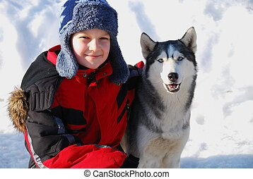 A Boy and his Dog in the Snow - A young boy and his dog in...