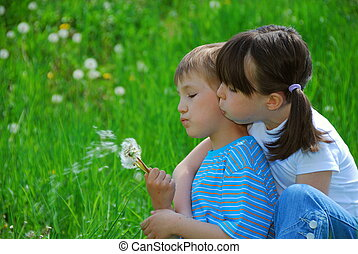 Kids blowing dandelion seeds - A cute view of a young...