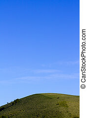 Green Hill, Blue Sky - Image of a dark green hill and bright...